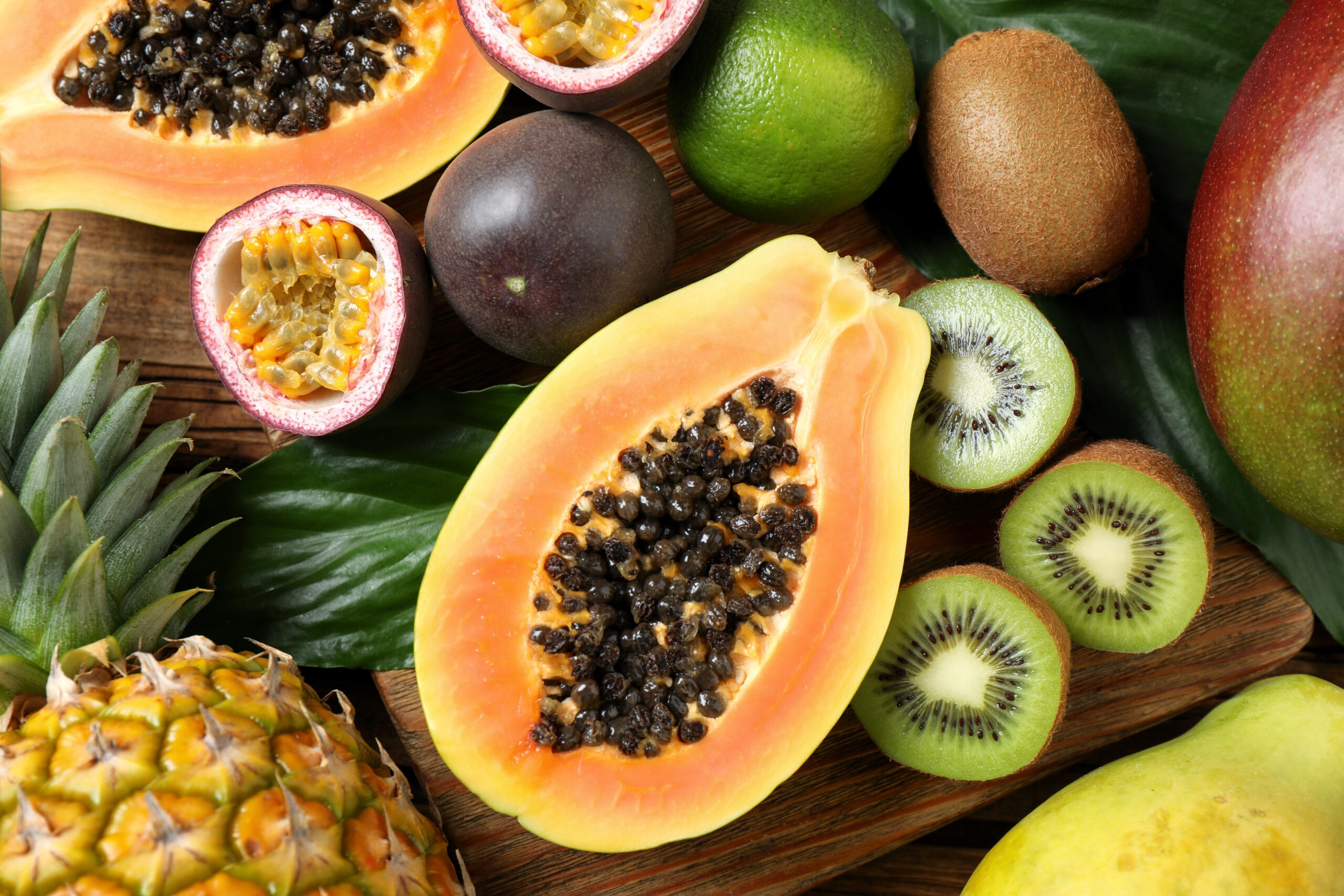 Fresh ripe papaya and other fruits on wooden table, flat lay